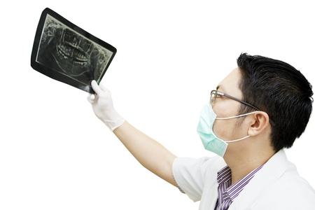 Portrait of asian dentist checking dental x-ray. isolated on white photo