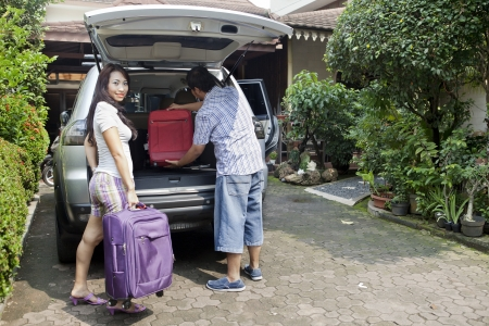 Smiling asian woman with her husband loading baggage in car, preparing for travel photo
