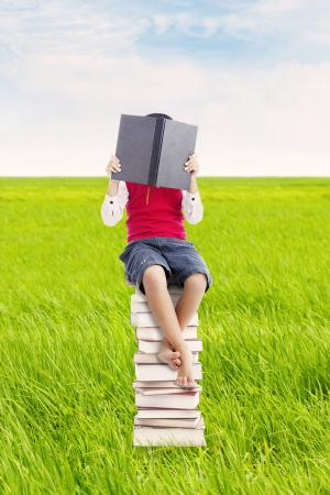 Elementary school student sitting on the stack of books and reads seriously. shot outdoor on the meadow photo