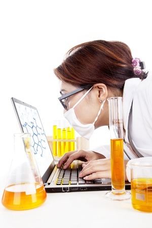 looking at watch: Lab assistant woman works with laptop and test-tubes in laboratory