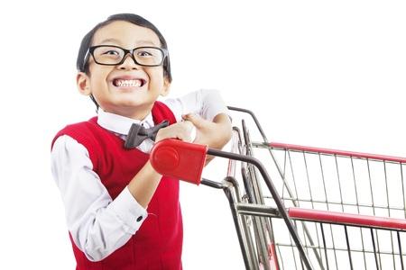 ni�o empujando: Sonriendo estudiante de escuela primaria con carrito de compras. rodada en el estudio aislado en blanco Foto de archivo