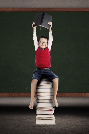child studying: Portrait of asian schoolboy holding a book and sitting on a stack of books in front of blackboard