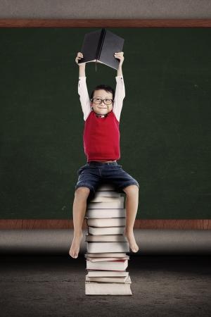 niños estudiando: Retrato del colegial asiático que sostiene un libro y sentarse en una pila de libros delante de la pizarra