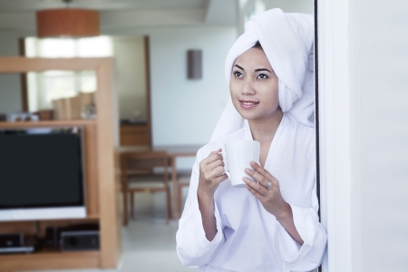 Asian woman wearing bathrobe holding cup of coffee at hotel room Stock Photo - 15193322