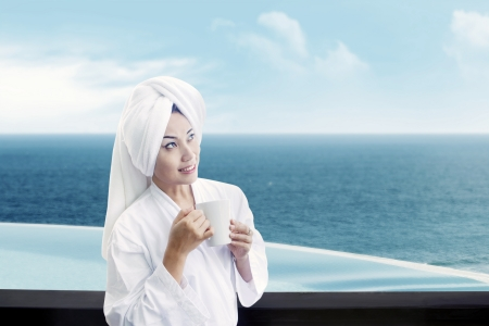 Portrait of asian woman wearing bathrobe and holding cup of coffee with background of ocean view Stock Photo - 15193335