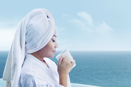 Asian woman in bathrobe drinking hot coffee with ocean view Stock Photo - 15193334