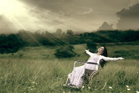 persona en silla de ruedas: Mujer asiática en silla de ruedas libertad abrazando al aire libre