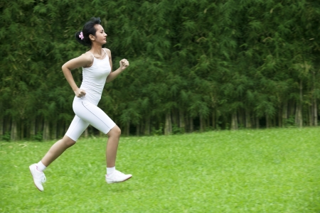 Healthy Lifestyle concept with Pretty woman running in the garden photo