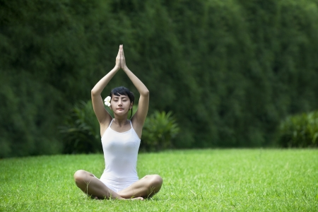 Beautiful Asian Woman meditating on grass. Shot in the garden during summer photo
