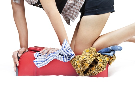 Woman standing on her knees on an overfilled suitcase with clothing.  photo