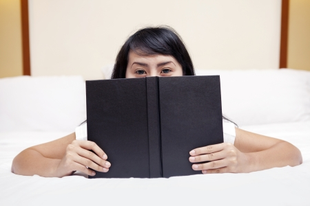 Young woman peeking from behind book, shot in the bedroom Stock Photo - 15193361