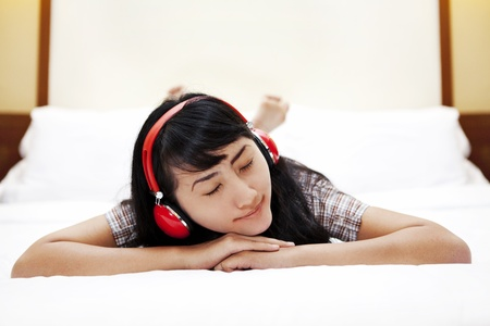 indonesian people: Cute Asian woman with a headphones listening to a music in a bedroom Stock Photo