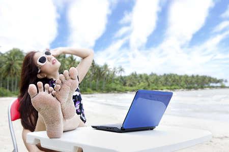 pies sexis: Joven empresaria asiática con la computadora portátil disfrutar de la playa hermosa. tiro al aire libre