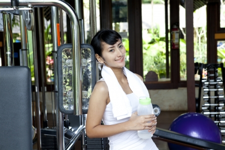 private club: Beautiful asian woman posing with towel and bottle of water in a gym