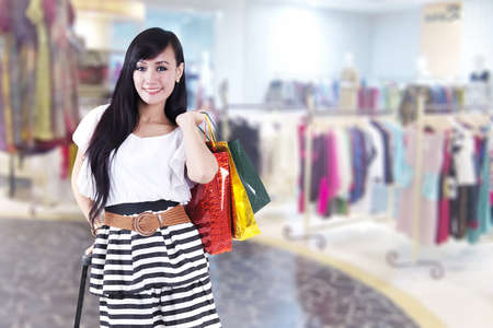 shopaholics: Asian woman brings a suitcase and shopping bags