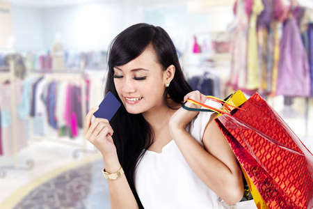 woman credit card: Pretty Asian woman carrying her shopping bag and a credit card ready to shop some more
