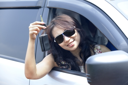 Young woman with glasses  showing a key to her new car photo