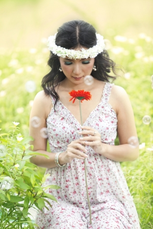 Pretty Asian woman holding a flower shot in meadow surrounded by bubble photo