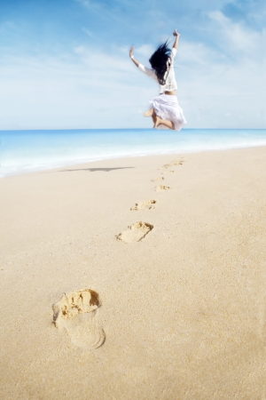 Portrait of woman with footprint enjoying freedom on beach. shot at tropical beach photo