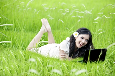 Spring and Summer Collection: Cheerful woman using laptop on green meadow  photo