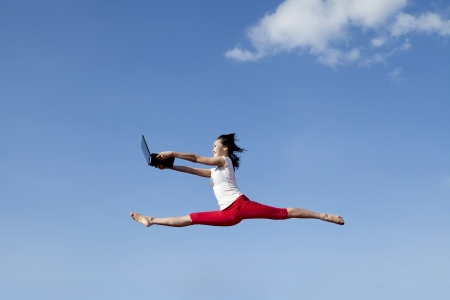 Woman holding a laptop computer jumping over blue sky photo