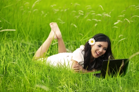 indonesia girl: Spring and Summer Collection: Cheerful woman using laptop on green meadow