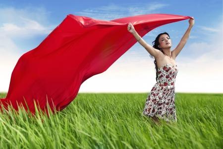 Mujer con pañuelo rojo con los brazos abiertos al aire libre expresión de la libertad