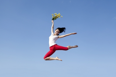 Pretty woman jumping while holding sunflowers. Shot over clear blue sky Stock Photo - 15193317