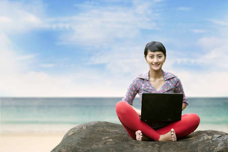 Beautiful woman working on laptop at the beach. Copy space is available for your text Stock Photo - 15193330
