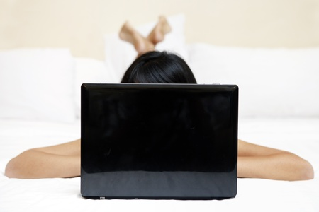 chat online: Photo of unrecognizable woman using laptop computer in a bedroom Stock Photo