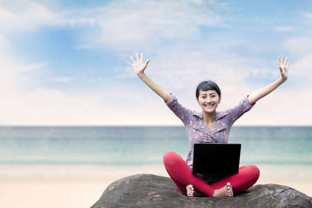 Pretty woman with laptop sitting on the stone under blue sky, shot at the beach  photo