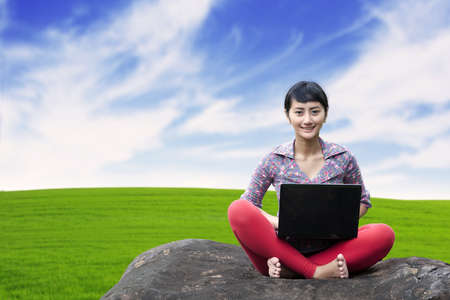 Pretty woman with laptop sitting on the stone shot at green grass background photo
