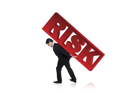 financial burden: Worried businessman carrying risk sign on his back. Shot in studio isolated on white