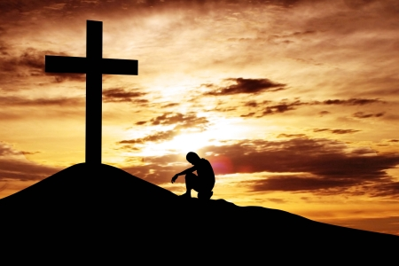 inginocchiarsi: Un uomo che fa una confessione alla croce, girato sotto il cielo dell'alba Archivio Fotografico