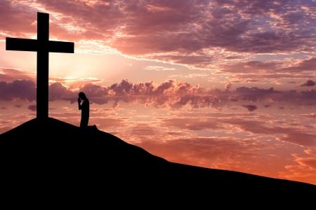 arrodillarse: Paisajes cielo dram�tico con una cruz de la monta�a y una silueta de hombre adorando a la cruz