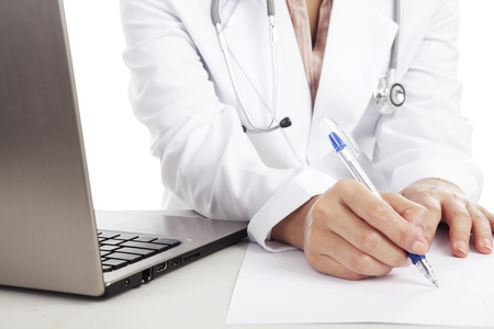 doctor's office: Doctor woman with stethoscope and laptop writing on the paper