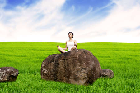 Pretty Asian woman meditating in nature under clear sky. shot in meadow Stock Photo - 15193419