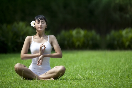Asian woman in yoga position shot outdoor during summer photo