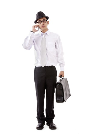 Young asian businessman carrying suitcase and calling on the phone isolated on white photo
