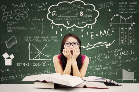 Stressed Asian student in a classroom  Shot against blackboard with formulas photo