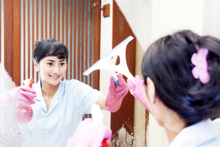 Beautiful Hotel maid wearing pink gloves cleaning up the mirror of bathroom photo