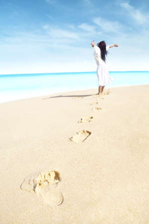 Carefree woman with footprints on the sand  shot at the tropical beach photo