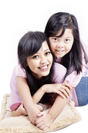 Portrait of cheerful mom and her child lying with pillow  shot in studio isolated on white photo