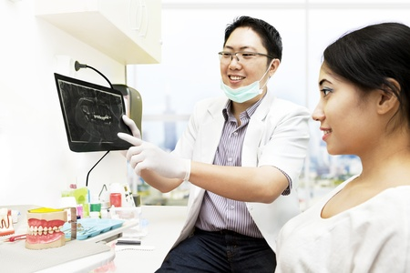 Asian dentist pointing to an x-ray while explaining about the patient photo