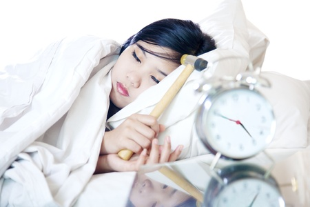 Portrait of asian woman with hammer smashing alarm clock from the Bed photo