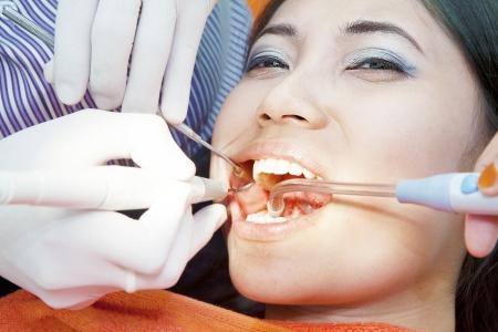 dolor de muelas: El tratamiento dental de la mujer asiática joven en la oficina del dentista Foto de archivo