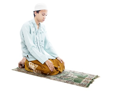 Portrait of asian muslim man praying on mat. shot in studio isolated on white photo