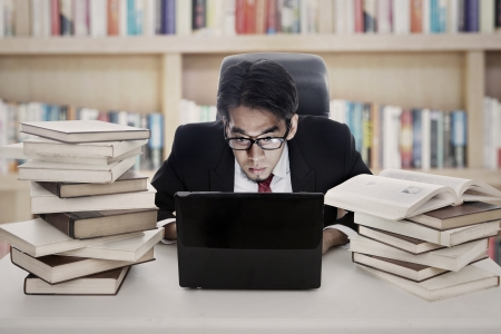 Portrait of asian employee works in library by using laptop computer photo