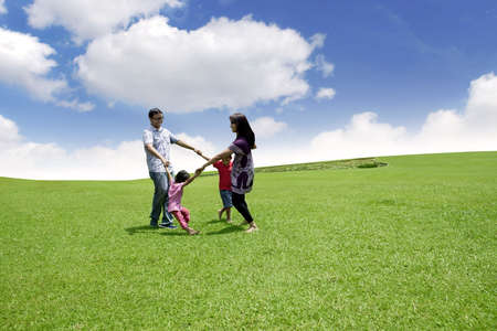 Happy asian family playing on the field. They are running in circle shot over blue sky  photo