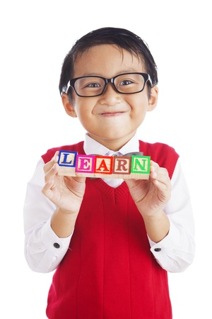 Asian elementary school student showing letter blocks spelling out LEARN. shot in studio isolated on white photo